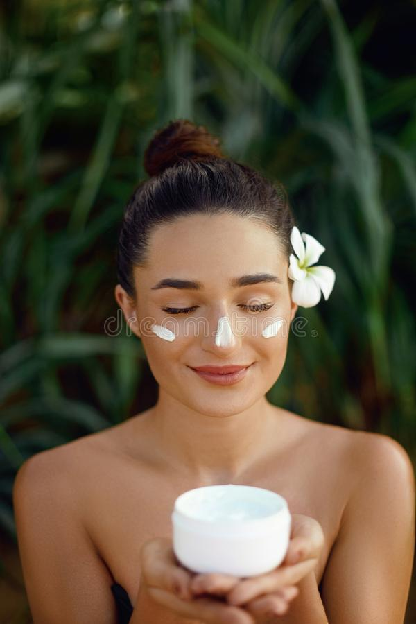 Beauty Face Skin care. Beautiful Woman with healthy smooth facial clean skin holding bottle cosmetic cream. Model with Beauty face royalty free stock images