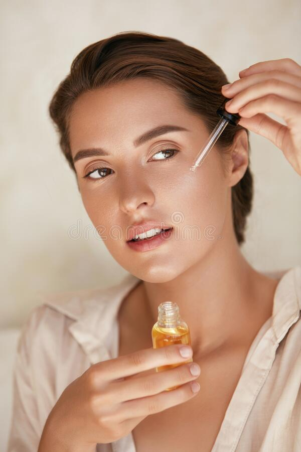 Free Beauty Face. Woman Applying Essential Oil On Facial Skin And Looking Away. Beautiful Model Moisturizing Derma. Royalty Free Stock Photos - 192845908