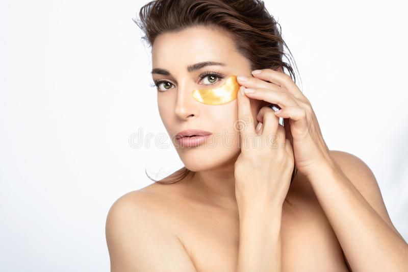 Beauty face woman applying a hydrogel eye patch on her flawless skin stock images