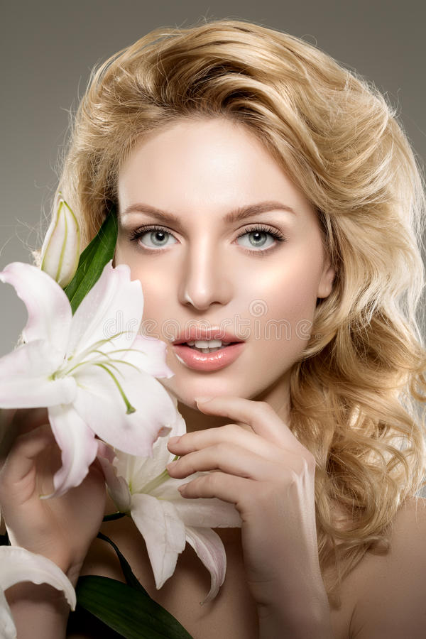 Beauty face woman, flowers, lily. Girl healthy model in spa salon. Cream treatment products. Facial skin terapy stock image
