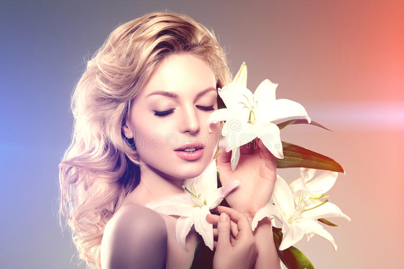 Beauty face woman, flowers, lily. Girl healthy model in spa salon. Cream treatment products. Facial skin terapy stock photo
