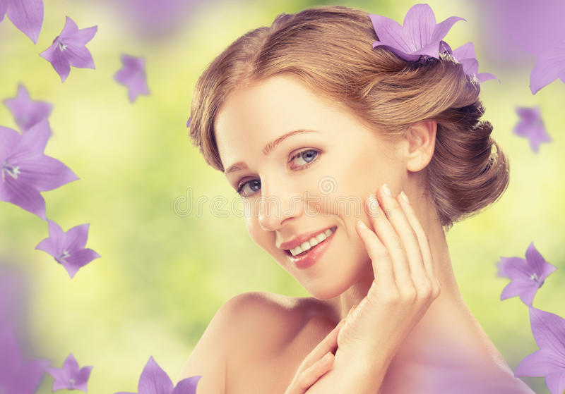 Beauty face of young beautiful healthy girl with purple and lilac flowers royalty free stock image