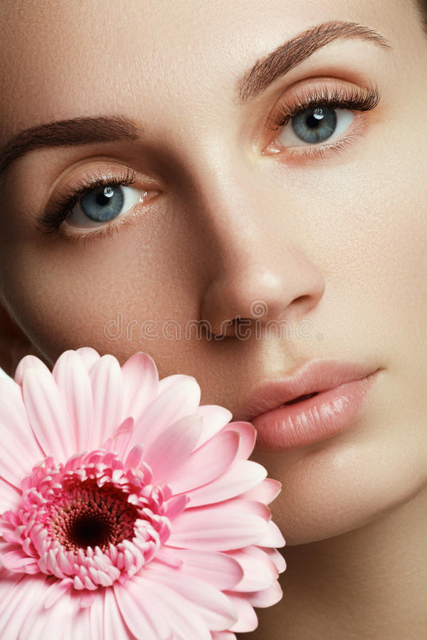 Beauty face of the young beautiful woman with flower. stock photos