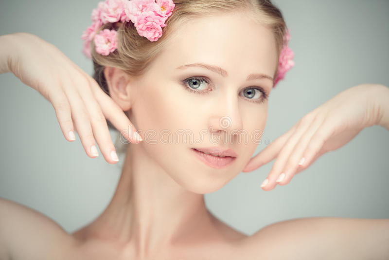 Beauty face of young beautiful woman with pink flowers royalty free stock images