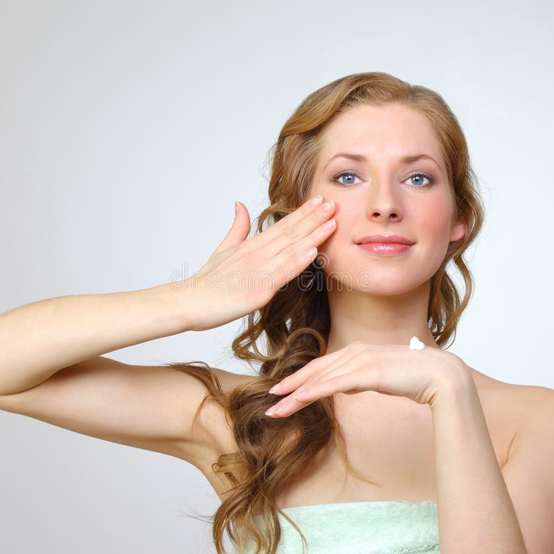 Beauty face of young woman with cosmetic cream stock photography