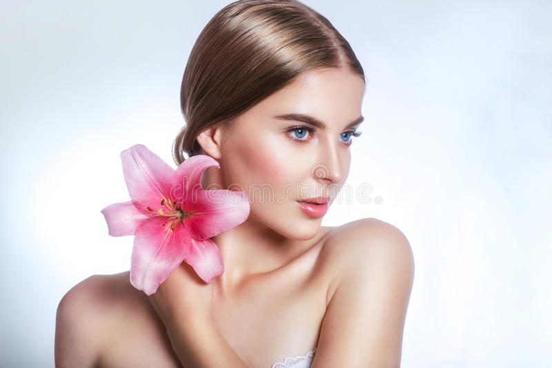 Beauty face of young woman with flower. Beauty treatment concept. Portrait over white background stock photo