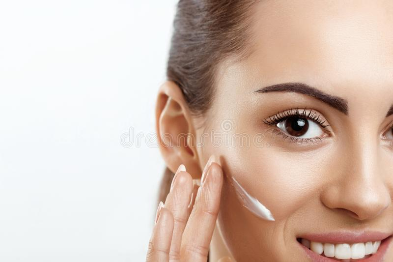 Facial Care. Female Applying Cream and Smiling.Portrait Of  Young Woman With Cosmetic Cream On Skin. Closeup Of Beautiful Girl stock image