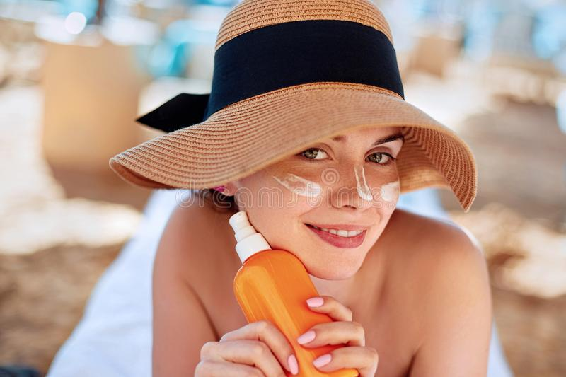 Beauty Facial Care. Young  Female Holding Bottle Sun Cream and  Applying on Face Smiling. Beauty Face. stock images