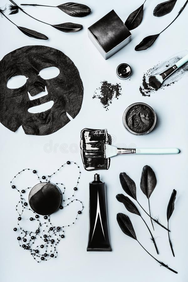 Beauty facial cosmetic products with Activated Charcoal: powder, Black head Mask, sheet mask and beauty tools accessories. Top view, flat lay. Modern skin stock image