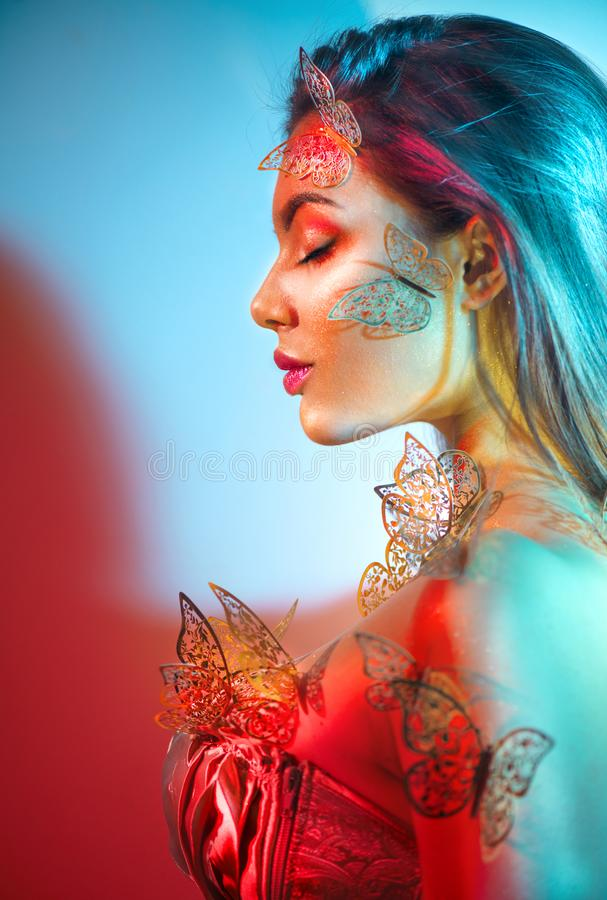 Beauty fantasy model spring girl in colorful bright neon lights. Portrait of beautiful summer young woman in UV. Art design. Colorful make up with golden royalty free stock photos