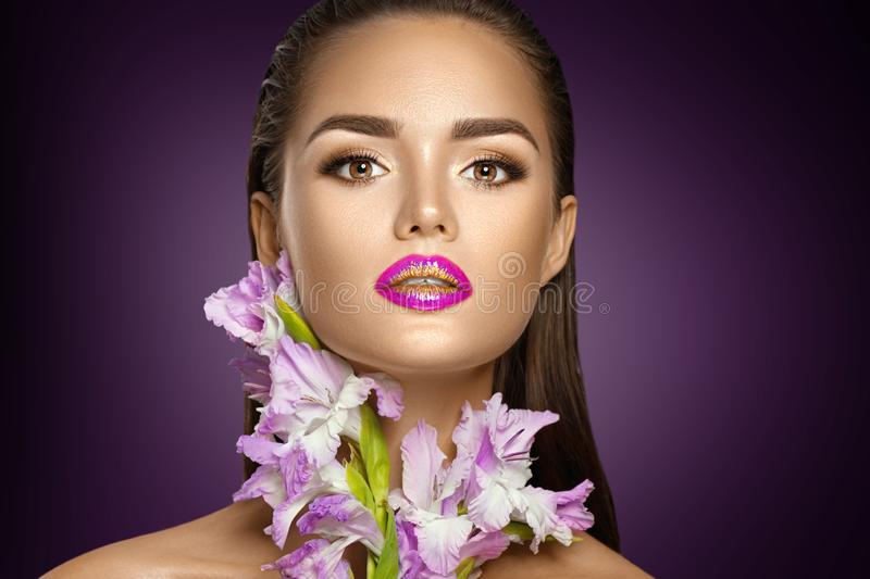 Beauty fashion brunette girl with gladiolus flowers. Glamour woman with perfect violet trendy makeup. Face contouring gradient lips royalty free stock photography