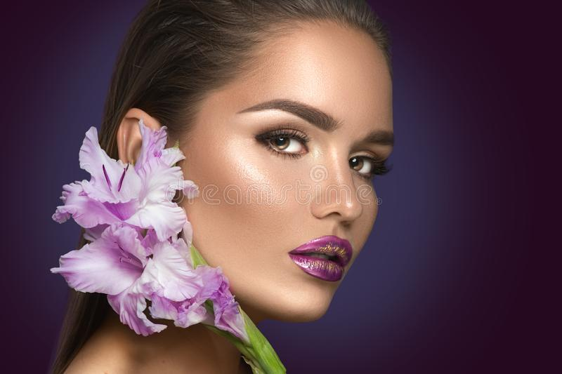 Beauty fashion brunette girl with gladiolus flowers. Glamour woman with perfect violet trendy makeup. Face contouring gradient lips royalty free stock photo