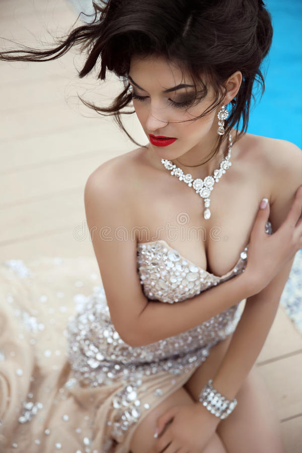 Beauty fashion brunette model portrait. Elegant lady in luxurious glamour dress with oriental gemstones and expensive jewelry. Ma. Keup. Hairstyle stock images