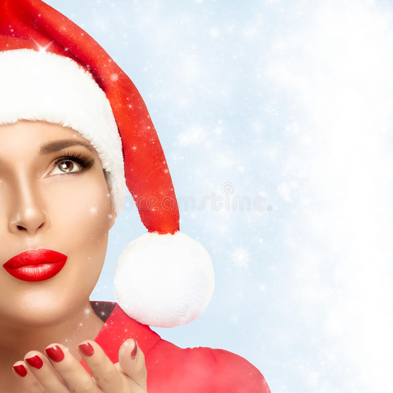 Beauty Fashion Christmas Woman in Santa Hat Looking Stardust Falling. Beautiful Christmas girl in Santa hat looking stardust falling. Red lips and manicure. Half royalty free stock images