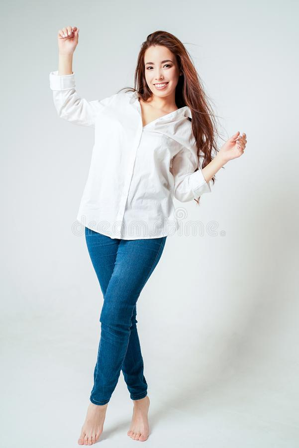 Beauty fashion full length portrait of smiling sensual asian young woman with dark long hair in white shirt on white background royalty free stock photography