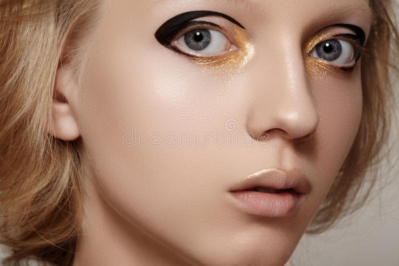 Beauty & Fashion. Girl Model Face With Bright Holiday Gold