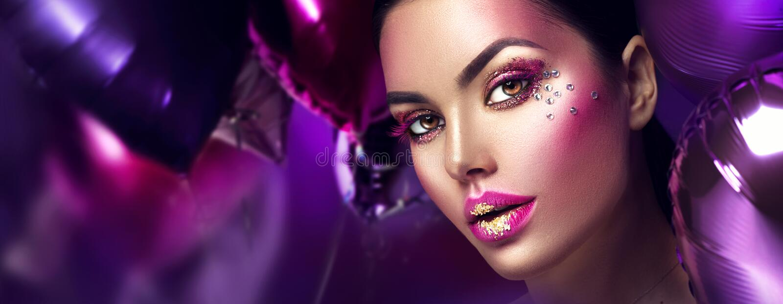 Beauty fashion model girl creative art makeup with gems. Woman face over purple, pink and violet air balloons. Background stock photos