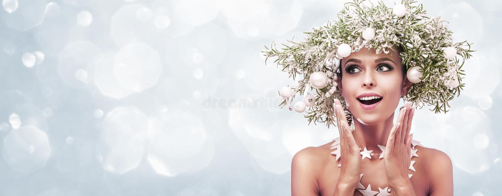 Beauty Fashion Model Girl with Fir Branches Decoration. Winter Hairstyle and Make Up royalty free stock photography