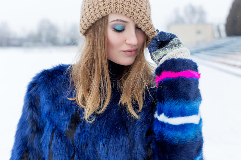 Beauty Fashion model girl in a fur coat Beautiful brunette woman with bright makeup in bright winter day stock photos