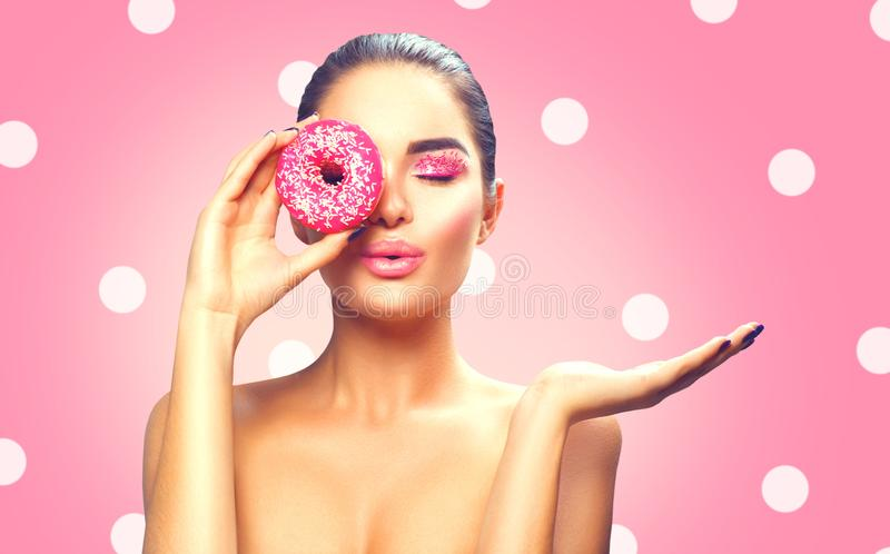 Beauty fashion model girl holding sweet pink colorful donut royalty free stock image