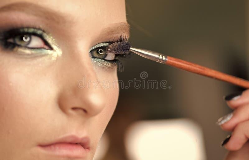 Beauty Fashion model girl. Fashion look. Woman mascara applying brush, female portrait makeup eyelashes.  royalty free stock image