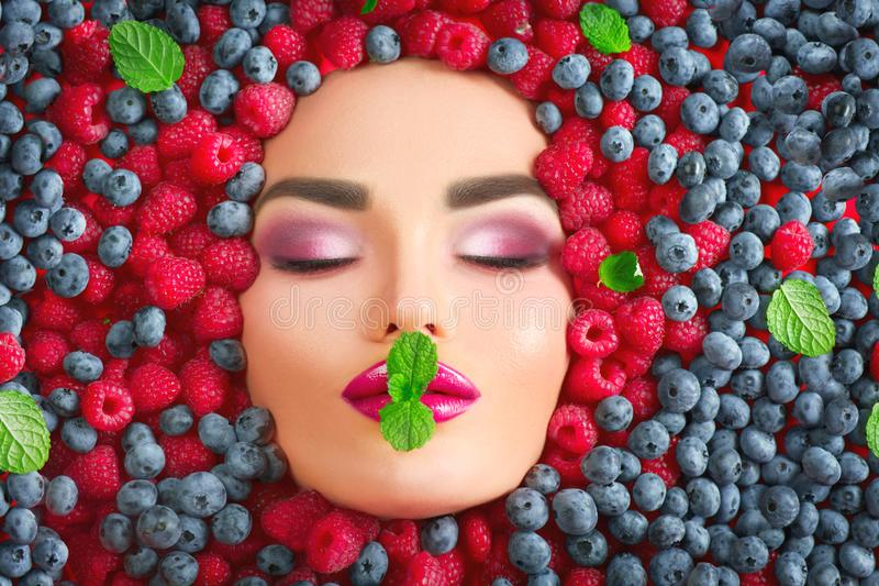 Beauty fashion model girl lying in fresh ripe berries. Face in colorful berries closeup. Beautiful makeup, juicy and lips. Pink eyeshadows stock photography