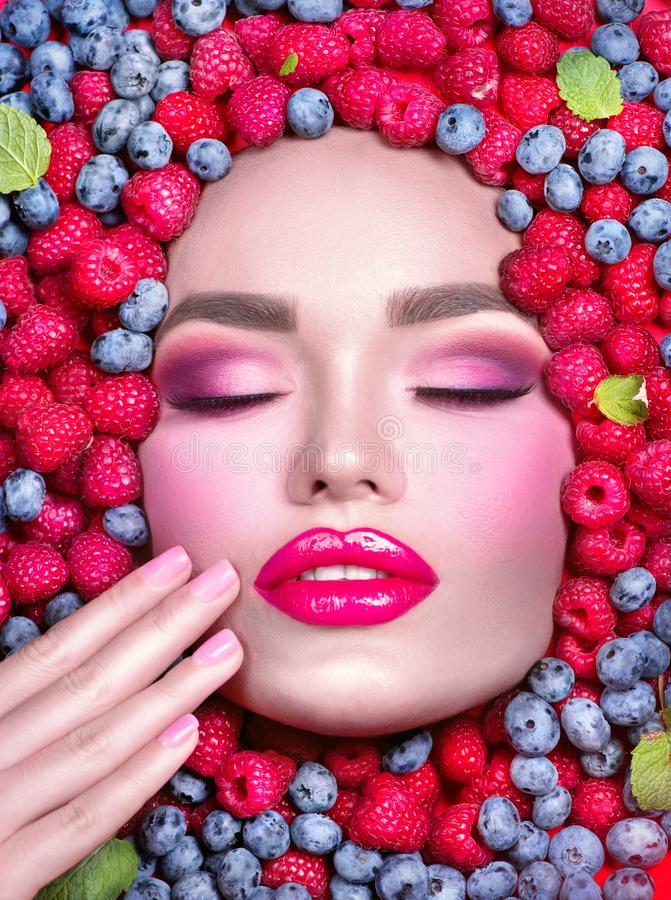 Beauty fashion model girl lying in fresh ripe fruits, berries and mint. Face in colorful berries close-up. Beautiful make-up royalty free stock images