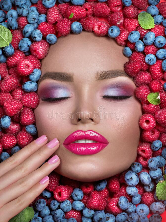 Beauty fashion model girl lying in fresh ripe fruits, berries and mint. Face in colorful berries close-up. Beautiful make-up royalty free stock photos
