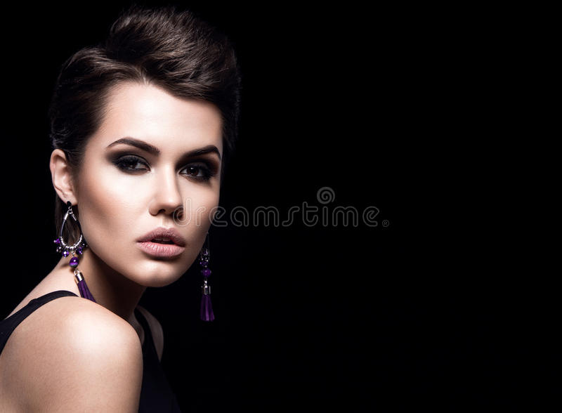 Beauty Fashion Model Girl with short hair. Brunette Model Portrait. Short haircut. Woman Makeup and Accessories. Isolated on black. Hair cut. Purple Earrings royalty free stock images