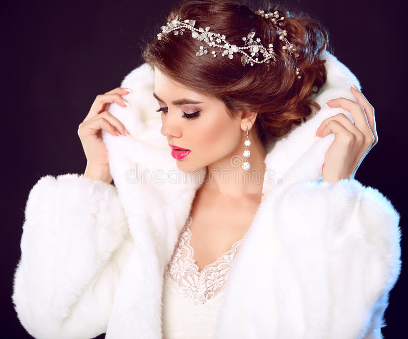 Beauty Fashion Model Girl in white Mink Fur Coat. Wedding hairstyle. Makeup. Beautiful Luxury Winter Woman isolated on dark stock photography