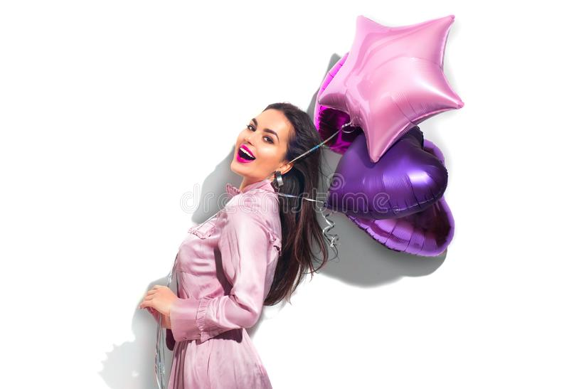 Beauty fashion model party girl with heart shaped air balloons having fun. Birthday party, Valentines Day. Beautiful young brunette woman over white background stock images