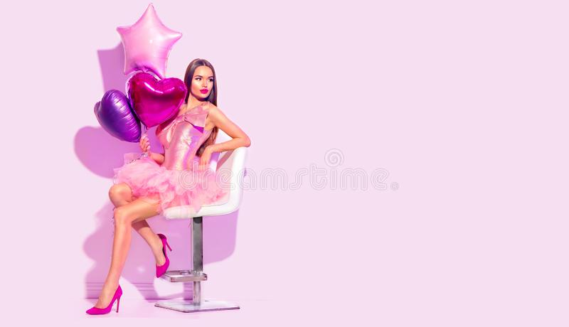 Beauty fashion model party girl with heart shaped air balloons posing, sitting on chair. Birthday party, Valentines Day stock image