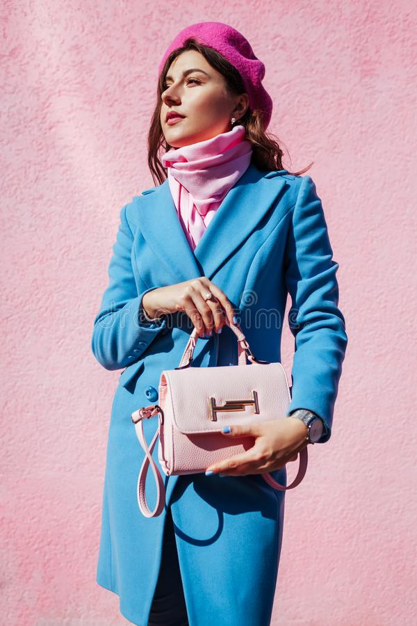 Beauty fashion model. Woman holding stylish handbag and wearing blue coat. Autumn female clothes and accessories royalty free stock photography