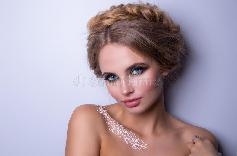 Beauty Fashion Model Woman , portrait, hairstyle with braids. Mehndi , white henna tattoo on shoulders. stock photography