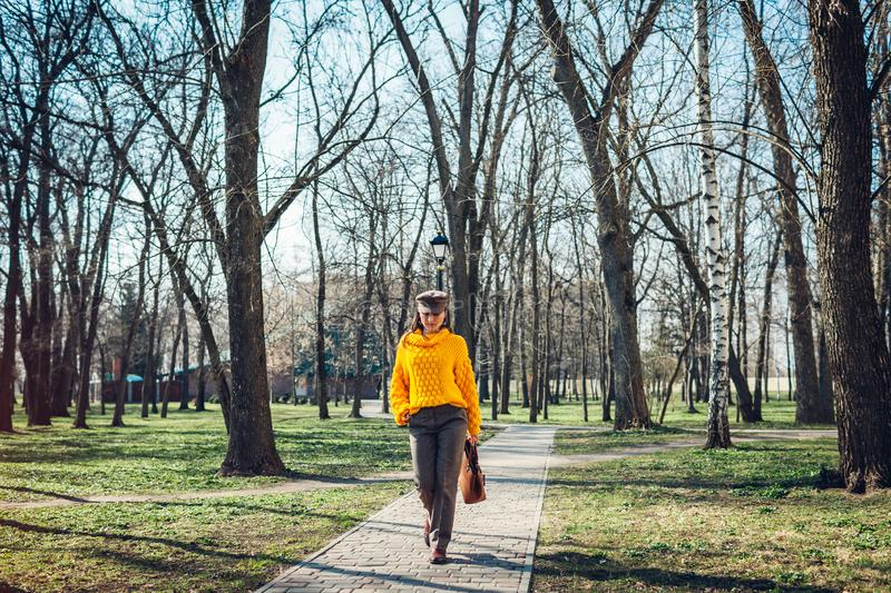 Beauty fashion model. Young woman holding stylish handbag and wearing yellow sweater. Autumn outfit. Clothes and accessories royalty free stock images