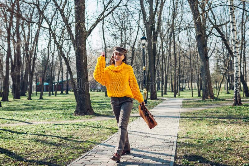 Beauty fashion model. Young woman holding stylish handbag and wearing yellow sweater. Autumn outfit stock photography