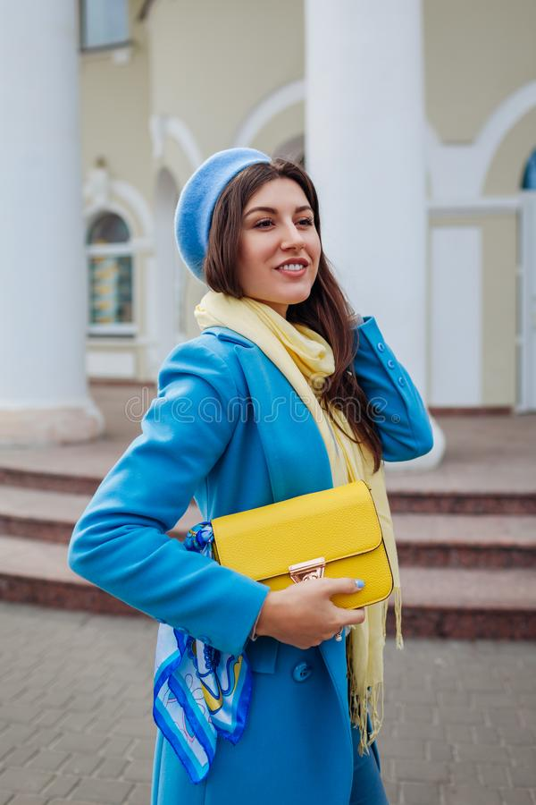 Beauty fashion model. Young woman in trendy blue coat holding stylish handbag. Autumn female clothes and accessories stock images
