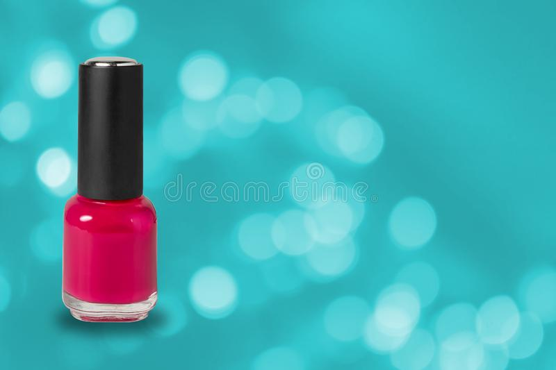 Beauty, fashion and nail art. Manicure art cosmetic tools, bottle of red colorful gel nail polish on blue bokeh background with royalty free stock image