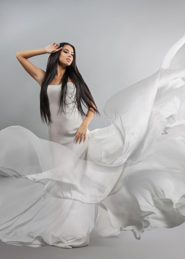 Beauty fashion photo of young beautiful girl in a flying white cloth. royalty free stock photography