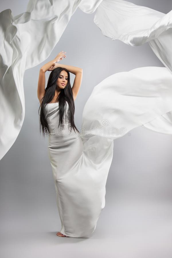 Beauty fashion photo of young beautiful girl in a flying white cloth. stock photo