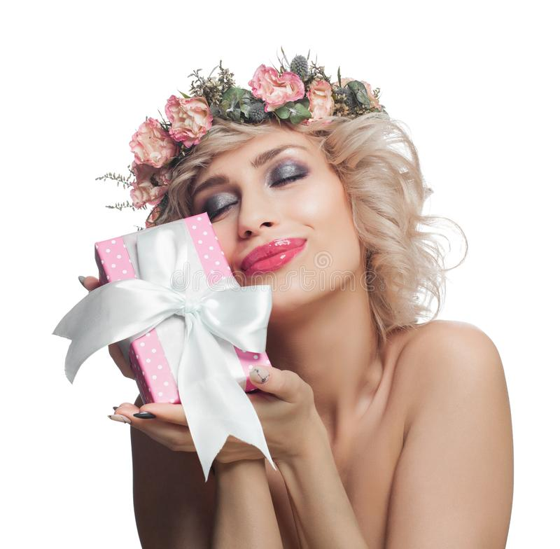 Beauty fashion portrait of beautiful woman enjoying gift. Pretty woman with blonde curly hair, makeup and flowers isolated royalty free stock photography