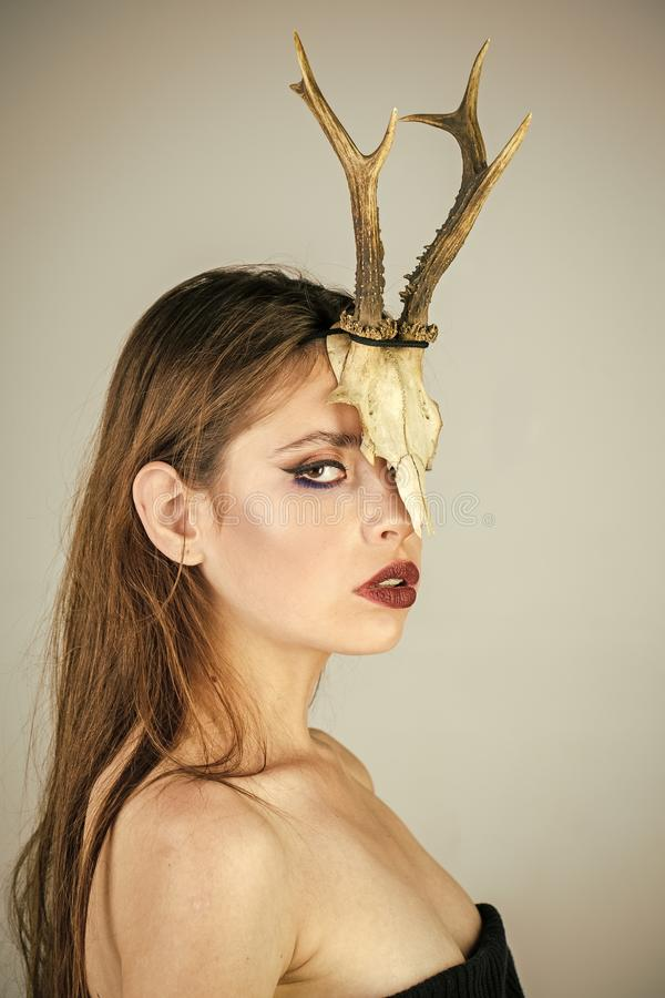 Beauty fashion portrait. Dark fantasy creature elf on halloween in skull. Woman with makeup and antlers. Fashion devil stock photos