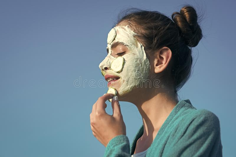 Beauty fashion portrait. Girl or woman apply cucumber mask on face. On blue sky. Beauty, nature, youth, skin care, rejuvenation concept, copy space royalty free stock photography
