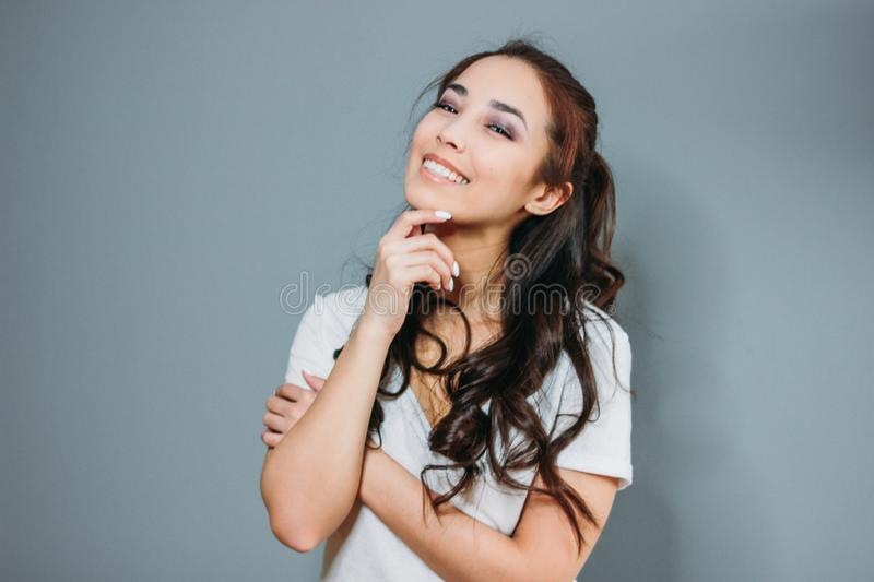 Beauty fashion portrait of smiling sensual asian young woman with dark long hair in white t-shirt on grey background royalty free stock images