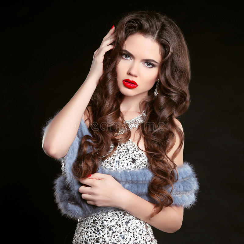 Beauty fashion portrait of young beautiful brunette girl in luxury dress with blue mink fur coat, woman with long healthy wavy ha stock images