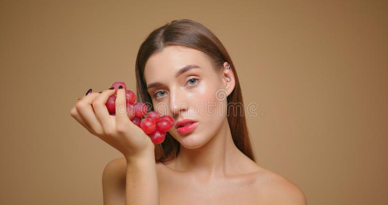 Beauty fashion portrait of young sensual brunette woman eating red grapes isolated on beige background royalty free stock image
