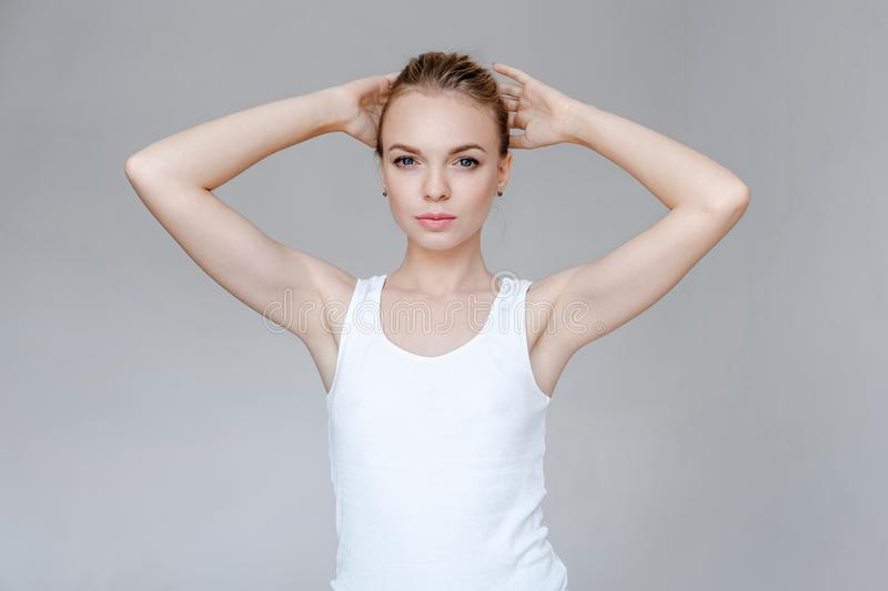 Beauty fashion portrait young woman with clear skin holds hands behind head royalty free stock photo