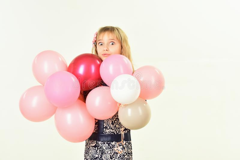 Beauty and fashion, punchy pastels. Little girl with hairstyle hold balloons. Birthday, happiness, childhood, look. Kid stock photo