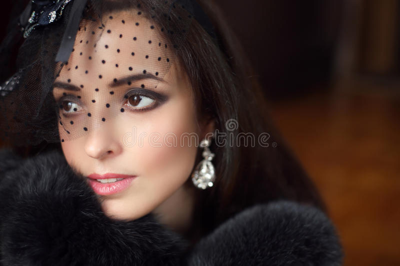Beauty fashion retro woman wearing little hat with veil and luxury fur coat, elegant female portrait. Makeup. Jewelry. royalty free stock photo
