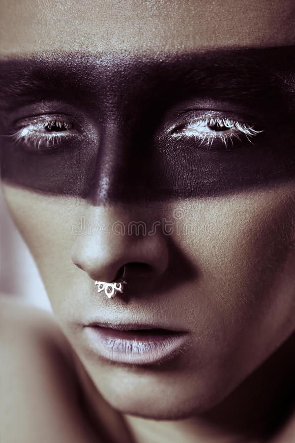 Beauty fashion shot of young man with nose rings and black strip line makeup and white eyelash. Male beauty portrait. Studio shot royalty free stock photography